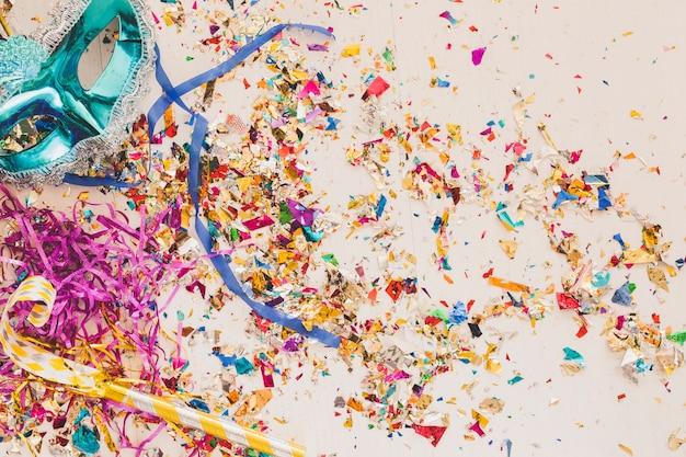 Confetti rougeoyant et masque de fête