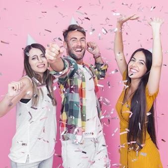 Confettis d'argent tombant sur les amis dansant sur fond rose