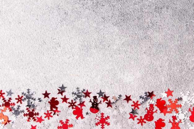 Confettis argentés et rouges sur l'espace de plâtre gris pour le texte