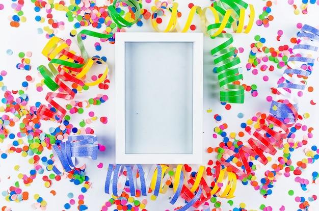 Confettis assortis colorés avec serpentine sur blanc