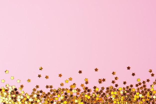 Confettis brillants sur fond rose