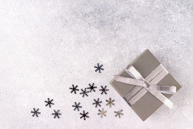 Confettis et coffret cadeau avec ruban de couleur argent sur fond gris
