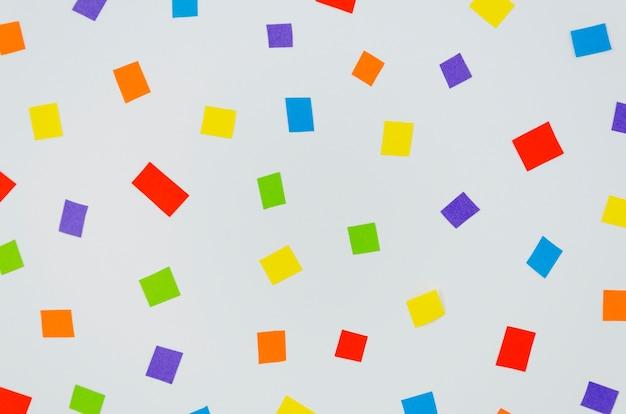 Confettis colorés au carré sur fond bleu