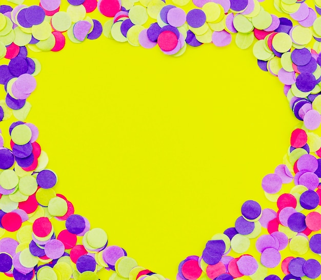 Confettis colorés sur fond jaune en forme de coeur