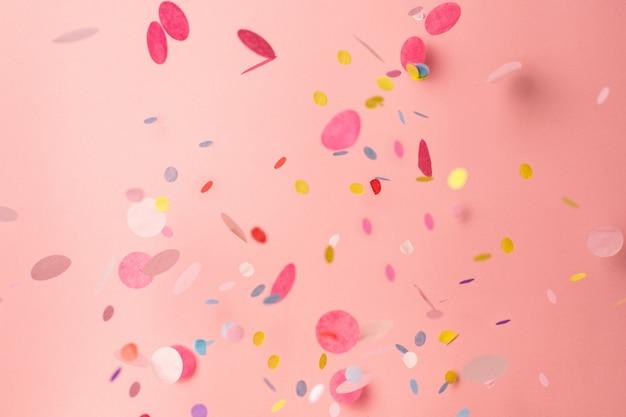 Confettis colorés sur fond rose pastel