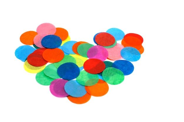Confettis colorés sous la forme d'un coeur sur fond blanc. fond, texture.
