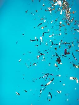 Confettis colorés tombant sur le bleu