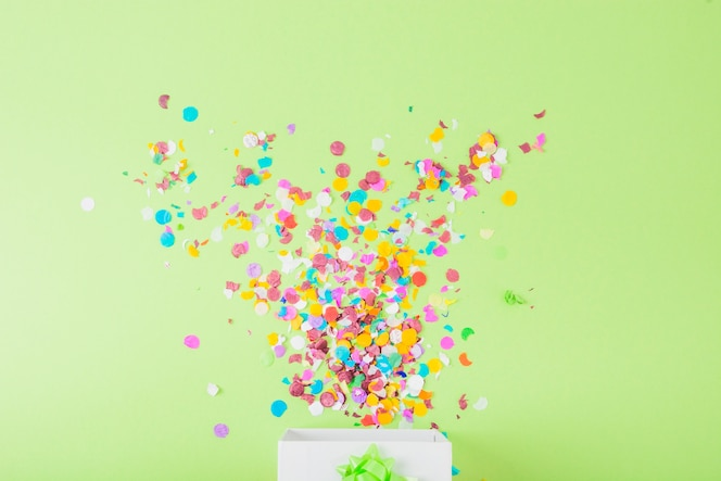 Confettis colorés tombant dans la boîte blanche sur la toile de fond vert
