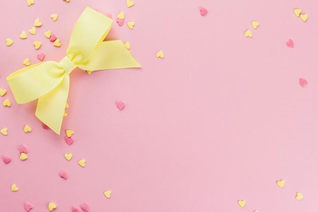 Confettis confiserie en forme de coeur jaune et rose et arc jaune sur un espace copie fond rose