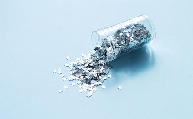 Confettis de couleur argentée tombant d'une bouteille en verre, matériel de bricolage ou de décoration de vacances