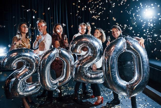 Confettis dans l'air. joyeux groupe de personnes avec des boissons et des ballons en mains célébrant la nouvelle année 2020.