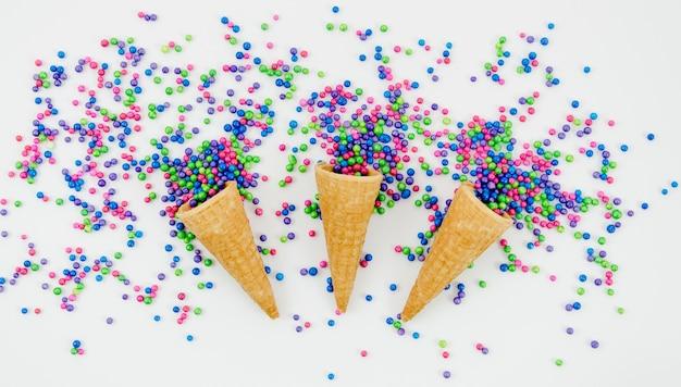 Confettis décoratifs vue de dessus avec des cônes de crème glacée