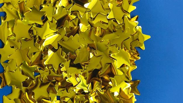 Confettis dorés à base d'étoiles sur bleu.