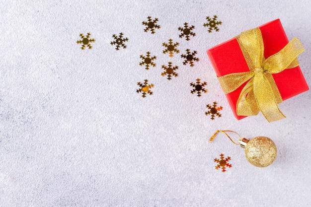 Confettis dorés, jouets de noël et coffret cadeau avec ruban sur fond gris