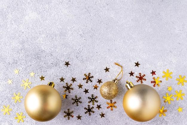 Confettis dorés, jouets de noël sur fond gris pour texte