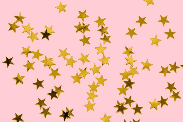 Confettis dorés sur une surface rose pastel