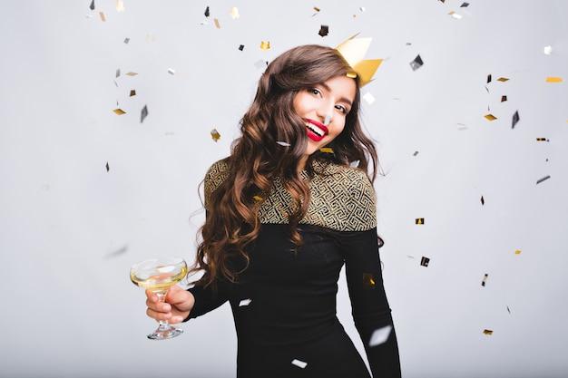 Confettis étincelants, émotions positives d'une fille incroyable excitée aux longs cheveux bouclés, couronne jaune s'amusant sur un espace blanc.