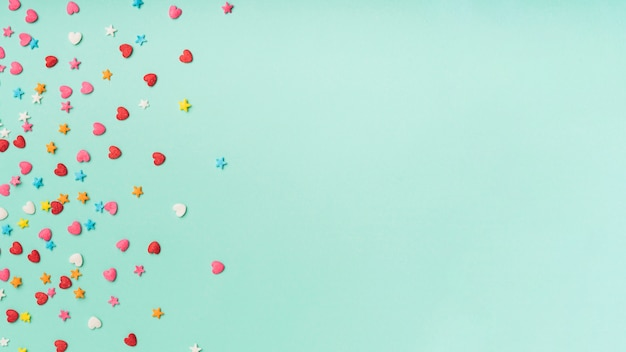 Confettis étoiles et coeurs sur fond turquoise avec espace copie