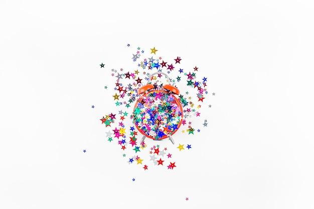Confettis étoiles de fête avec le concept de réveil rouge
