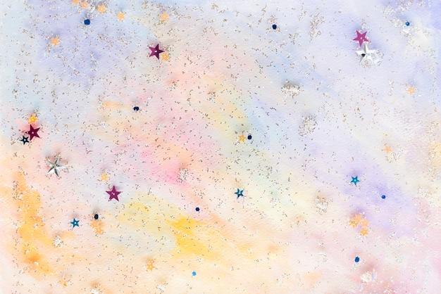 Confettis étoiles pailletées sur fond aquarelle pastel abstrait coloré
