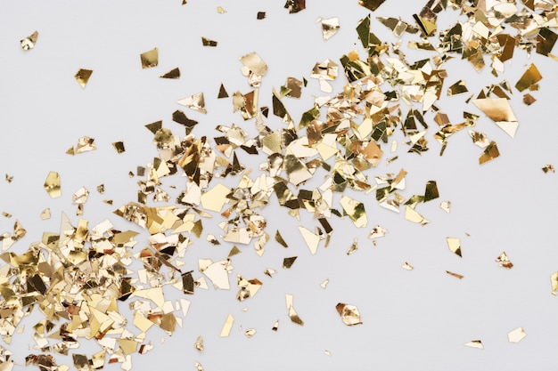 Confettis de feuilles d'or sur fond blanc. fond de paillettes étalées en diagonale.