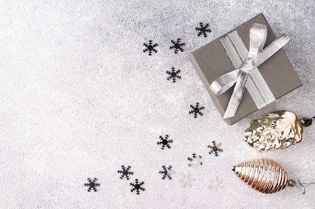 Confettis, jouets de noël et coffret cadeau avec ruban argenté sur fond gris