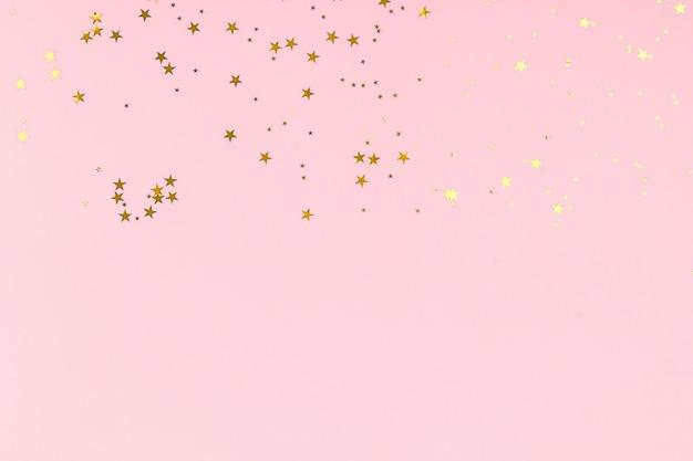 Confettis de paillettes étoiles dorées sur fond rose. décor festif.