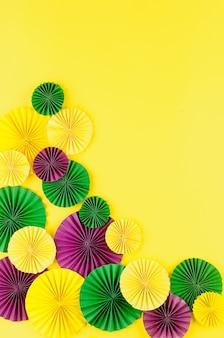 Confettis en papier coloré, masque de carnaval et serpentine de couleur sur fond jaune