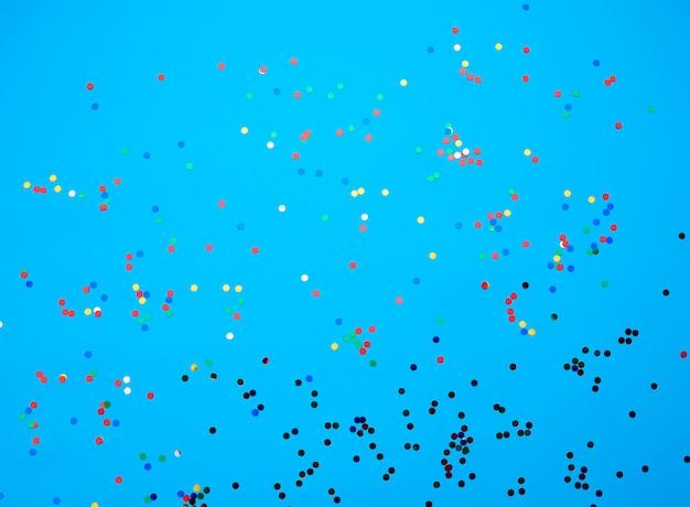 Confettis ronds multicolores brillants éparpillés sur un fond bleu