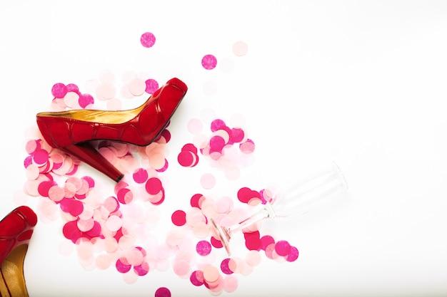 Confettis roses, chaussures rouges pour femmes et un verre de champagne vide sur fond blanc. concept après la fête. matin après la fête. mise à plat, vue de dessus