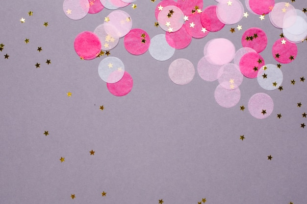 Confettis roses avec des étoiles d'or sur gris avec fond