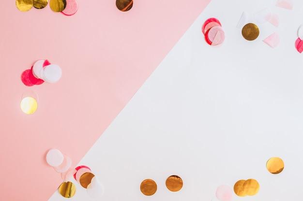 Confettis roses et étoiles et scintille sur fond rose. vue de dessus. fond de vacances festives.