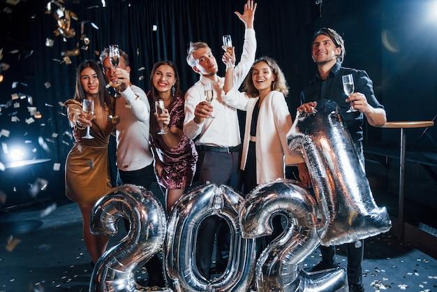 Des confettis sont dans l'air. joyeux groupe de personnes avec des boissons et des ballons à la main célébrant la nouvelle année 2021.