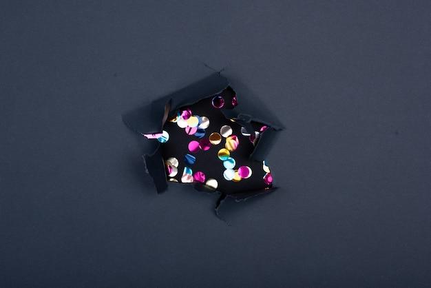 Confettis tirés en l'air lors d'une fête sur la plage. seuls les confettis sur fond noir de la nuit. confettis vert et rouge