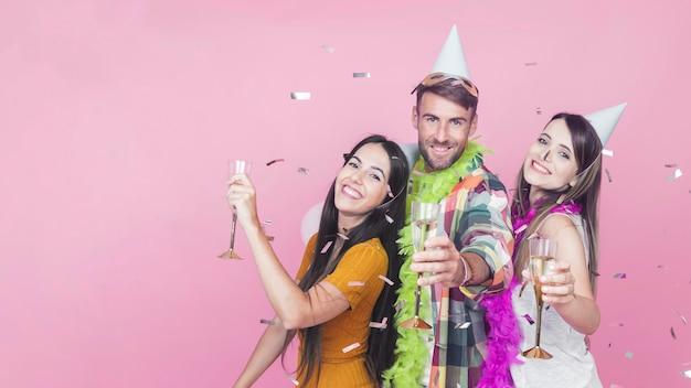 Confettis tombant sur des amis heureux, tenant des boissons sur fond rose