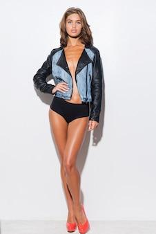 Confiance et beauté. toute la longueur de la belle jeune femme portant une veste cool sur le corps nu