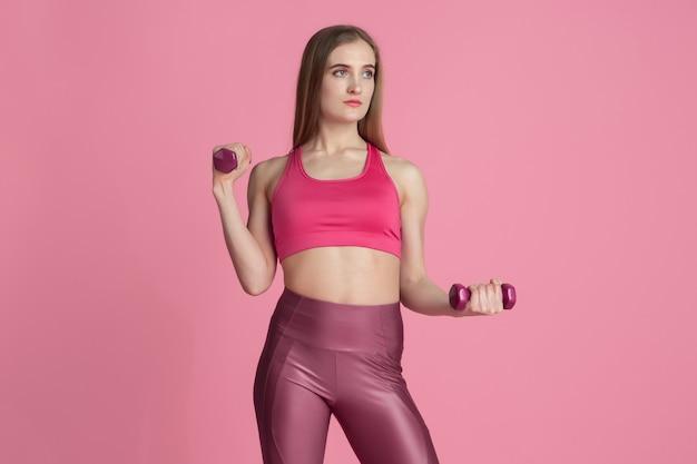 Confiance. belle jeune athlète féminine pratiquant, portrait rose monochrome. modèle caucasien de coupe sportive avec poids. musculation, mode de vie sain, concept de beauté et d'action.