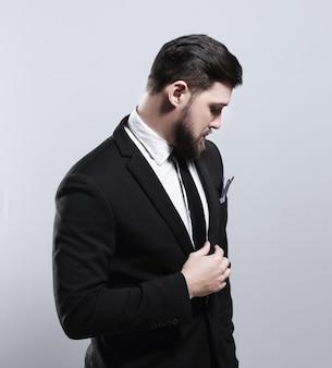 Confiance et charisme beau jeune homme en costume complet ajustant sa veste
