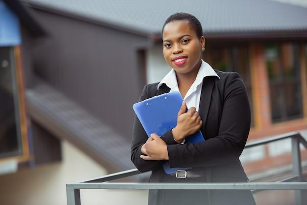 Confiance. femme d'affaires afro-américaine en tenue de bureau souriante, a l'air confiante et heureuse, occupée. concept de finance, d'entreprise, d'égalité et de droits de l'homme. belle jeune femme modèle, réussie.