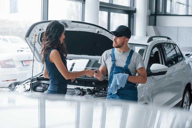 Confiance et occupation. femme dans le salon de l'automobile avec un employé en uniforme bleu en prenant sa voiture réparée en arrière