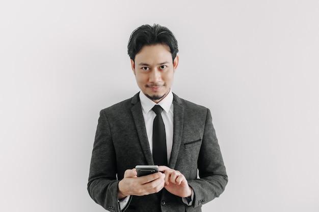 La confiance et le visage réussi de l'homme d'affaires utilisent l'application téléphonique
