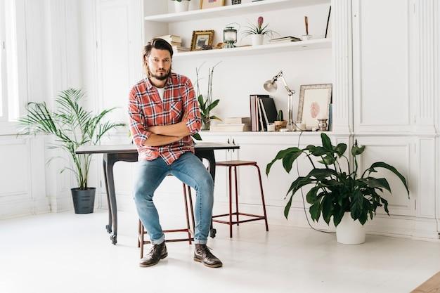 Confiant beau jeune homme assis sur un tabouret à la maison avec ses bras croisés