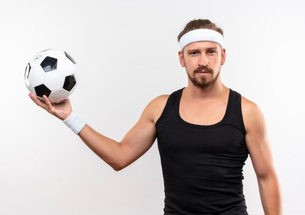 Confiant, beau, jeune, sportif, homme, porter, bandeau, et, bracelets, tenue, ballon football, regarder, isolé, blanc, mur