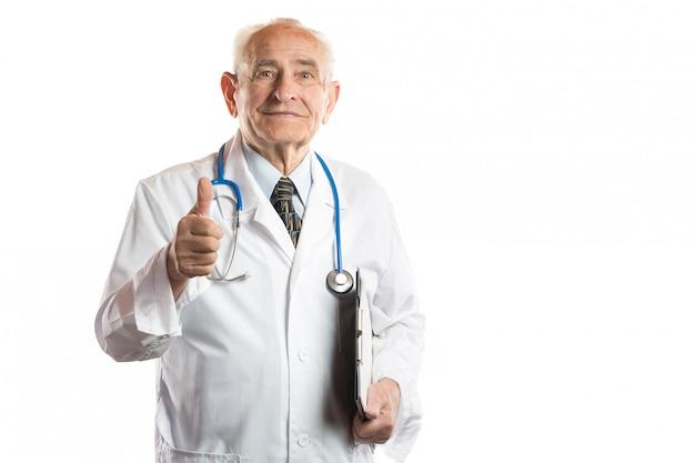 Confiant et beau médecin senior souriant ou professeur avec stéthoscope et dossier de documents montrant les pouces vers le haut isolé sur blanc
