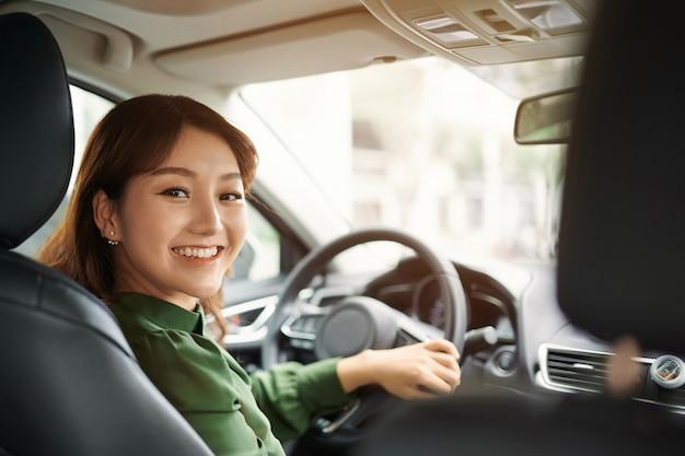 Confiant et beau. vue arrière d'une jeune femme séduisante en tenue décontractée regardant par-dessus son épaule en conduisant une voiture
