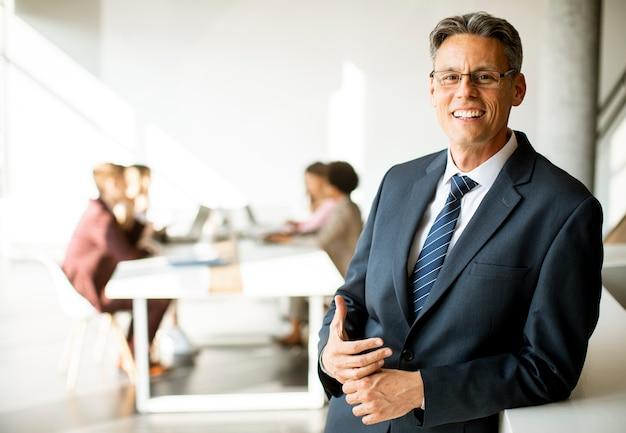 Confiant bel homme d'affaires debout au bureau