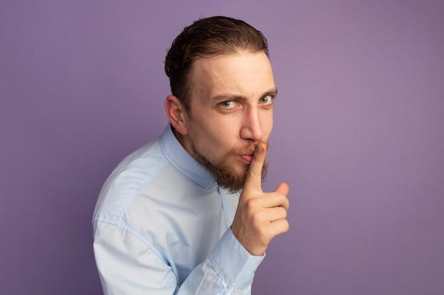 Confiant bel homme blond faisant le geste de silence isolé sur mur violet