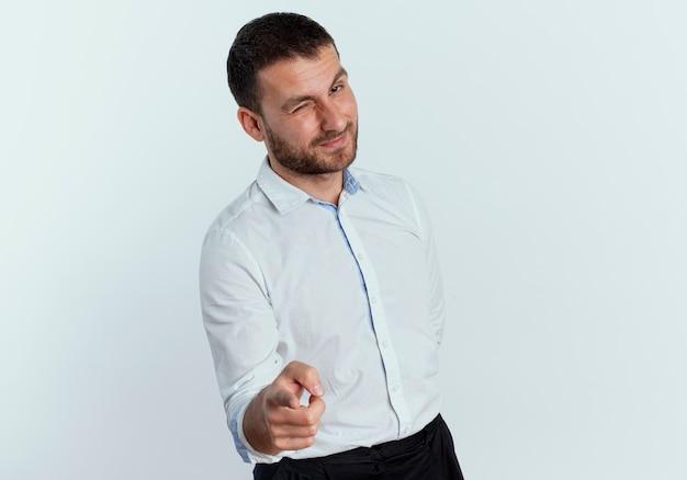 Confiant bel homme clignote des yeux et des points isolés sur un mur blanc
