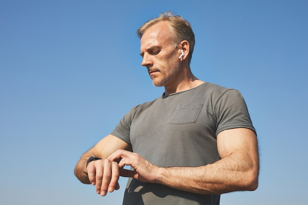 Confiant bel homme mûr dans les écouteurs debout contre le ciel bleu et prendre le pouls avec smartwatch