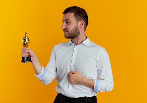 Confiant bel homme tient et regarde la coupe du gagnant isolé sur un mur orange